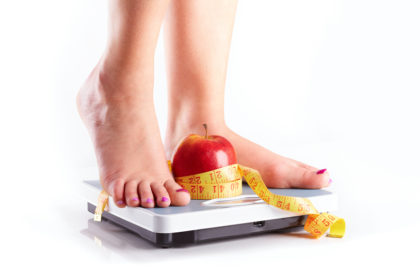 A pair of female feet standing on a bathroom scale with red apple and tape measure between them